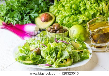 Green salad and ingredients - lettuce, avocado, olives, oil, herb and onion on white background. Vegetarian or healthy eiting concept