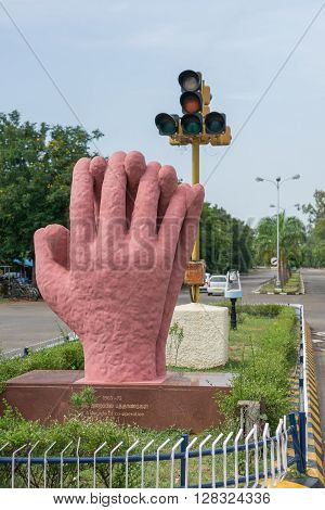 Trichy India - October 15 2013: Solidarity and cooperation monument along main boulevard of the city. Two large pink hands joining together with traffic lights as background.