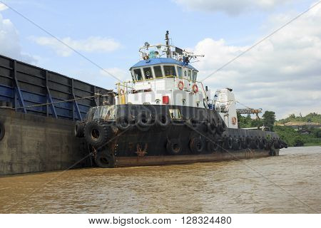 Tug boat on side of the empty barge