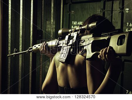 Girl holding on her shoulders svd sniper rifle. Rear view.