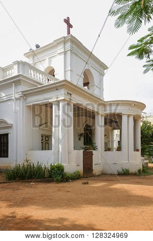 Trichy India - October 15 2013: Altar side of St. John's Anglican Church. White one-story sanctuary built in 19th century. Plants surrounds. Cross on top.