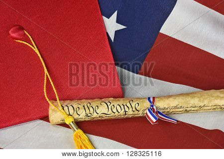 Red graduation cap and gold tassel with vintage American constitution on flag