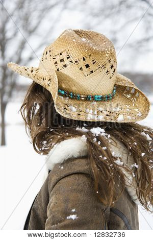 Back view of brunette woman with long hair wearing straw cowboy hat outdoors.