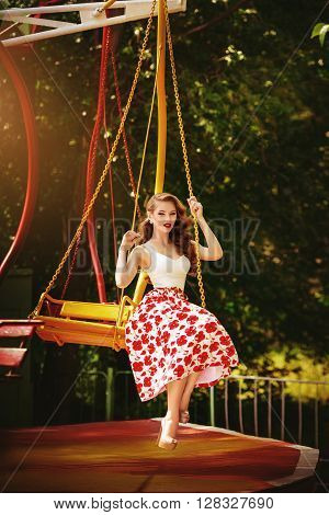 Beautiful young girl in the Park about colorful carousels