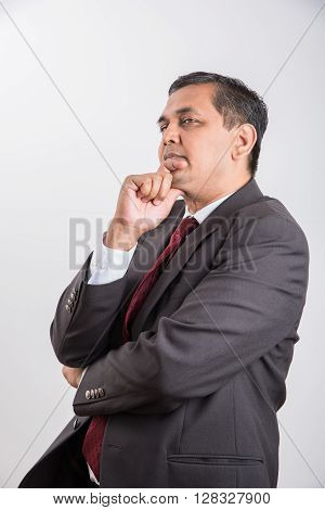 indian mid age businessman thinking, handsome asian businessman thinking, indian businessman with one hand folded and one hand touching chin, thinking, isolated over white background