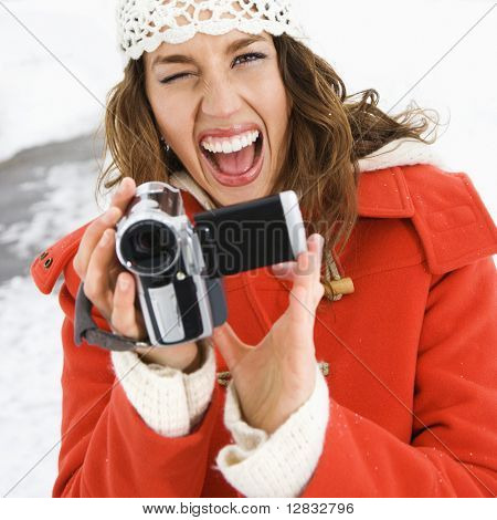 Caucasian young adult female in winter clothing pointing digital camera at viewer and winking.