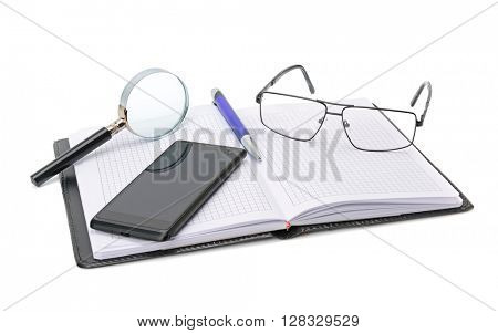 Notebook, glasses, cell phone and magnifying glass isolated on white