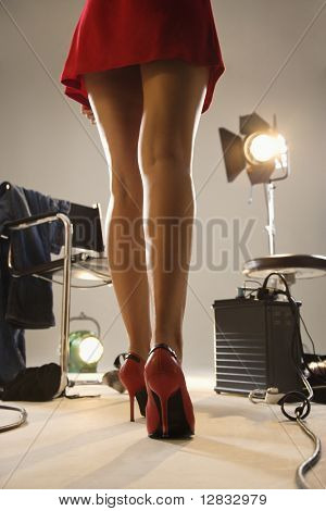 Low angle of young sexy woman's legs with photography studio equipment.