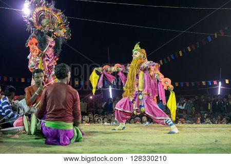 BAMNIA PURULIA WEST BENGAL INDIA - DECEMBER 23RD 2015 : Masked Dancers performing at Chhau Dance festival resurrecting a demon at night. Shot under colored lights. It is a Indian tribal martial dance based on Hindu myth.