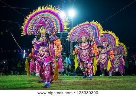 BAMNIA PURULIA WEST BENGAL INDIA - DECEMBER 23RD 2015 : Four masked dancers performing at Chhau Dance festival shot under colored lights. It is a very popular Indian tribal martial dance performed at night amongst spectators.