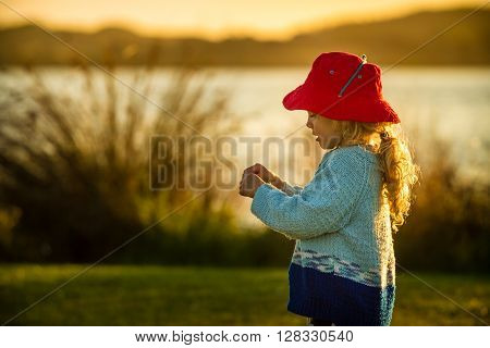 close up of a a four year old child wearing a bright red hat playing happily at sunset on the shore of a lake