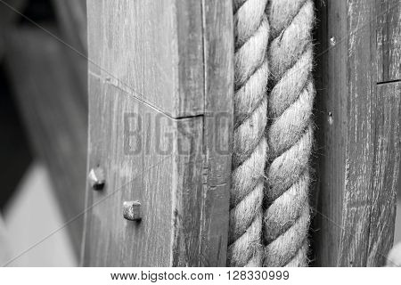 big hempen rope on the old wooden coil a closeup of monochrome tone