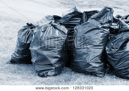 big black plastic bags are filled with garbage and located on open space for loading and export on utilization