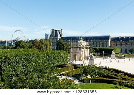 Color DSLR stock image of a lush, green courtyard, Paris, France, with a ferris wheel in the background. Horizontal with copy space for text