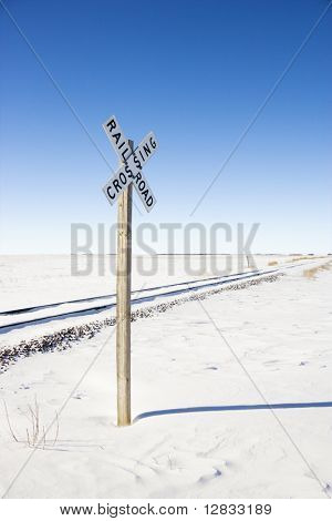 Railroad crossing sign by tracks in rural desolate snowy landscape.