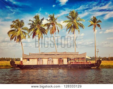 Kerala India tourism travel concept background - vintage retro effect filtered hipster style image of Houseboat on Kerala backwaters. Kerala, India