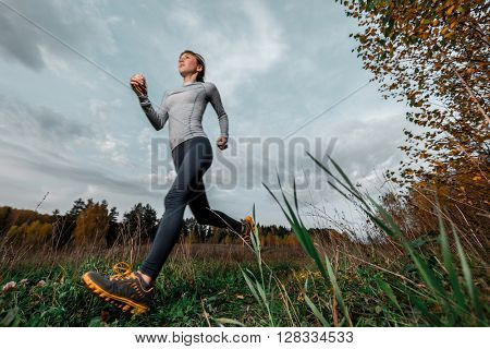 Woman in sportswear running along the path in autumn forest with motion blur