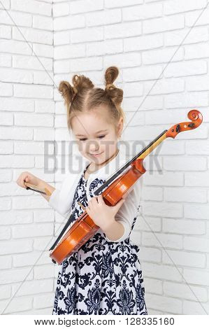 little girl holding a violin and looking at her