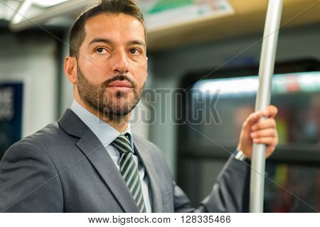 Businessman hanging to a pole in a train in the subway