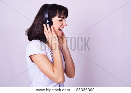 Music. Young hispanic woman listening to music with headphones. Playful smiling woman isolated over grey background.
