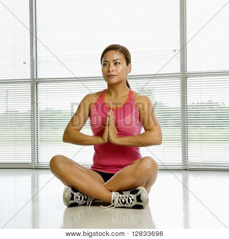 Mid adult Asian woman sitting in yoga lotus position with palms together.