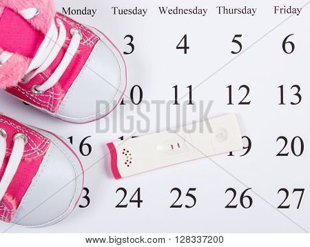Pregnancy test with positive result and baby shoes lying on calendar concept of extending family and expecting for baby