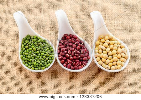 Mix of seeds beans green bean azuki or red bean soy bean on in white spoon on sack background.