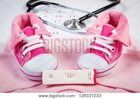 Pregnancy test with positive result clothing for newborn and stethoscope on calendar baby shoes bodysuits concept of extending family and expecting for baby