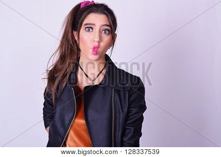 Portrait of fashionable young woman wearing stylish urban clothes. Fashion studio portrait over grey backgroung.