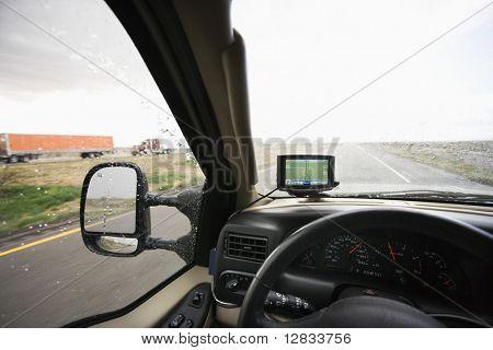 Fahrzeug-Armaturenbrett mit GPS und Blick durch die Windschutzscheibe des verregneten Autobahn voran.