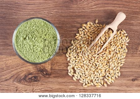 Heap of young powder barley and barley grain with scoop on wooden background healthy nutrition and lifestyle body detox