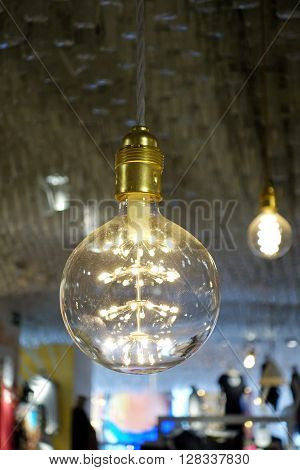 Close-up of retro glowing light bulb hanging from a ceiling