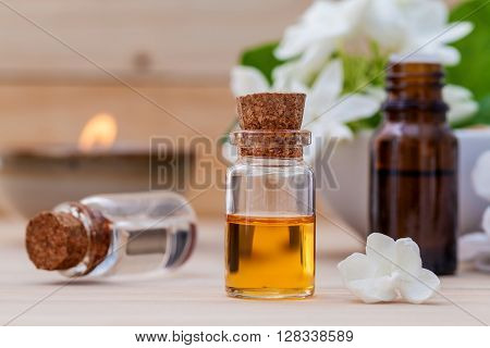 Bottle Of Essential Oil And Jasmin Flower With Shallow Depth Of Field Setup On Wooden Background .
