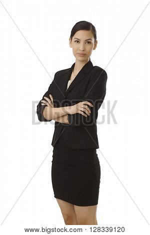Young attractive businesswoman standing arms crossed, smiling.