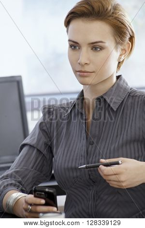 Attractive young businesswoman holding mobilephone, daydreaming.