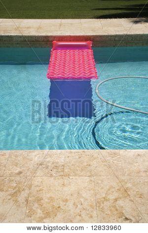 Flotador rosa y manguera de aspiración en la piscina.
