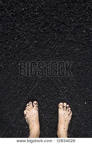 Man's barefeet in black sand in Maui, Hawaii.