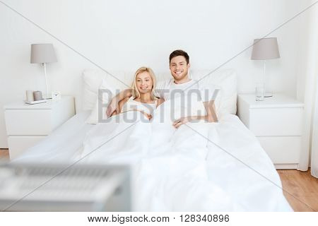 people, rest, love, relationships and happiness concept - happy couple lying in bed at home and watching tv
