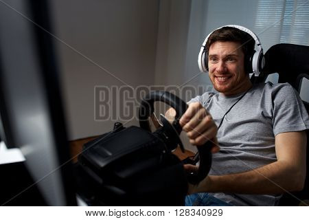 technology, gaming, entertainment and people concept - happy smiling young man in headphones with pc computer playing car racing video game at home and steering wheel