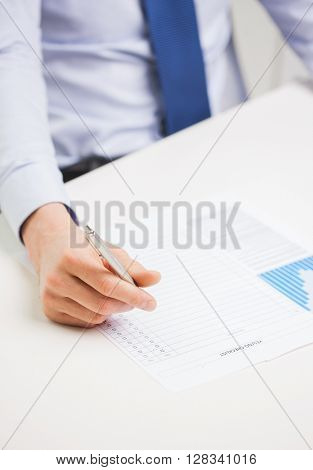 business, paperwork, statistics and people concept - close up of businessman hand with charts and pen filling form in office