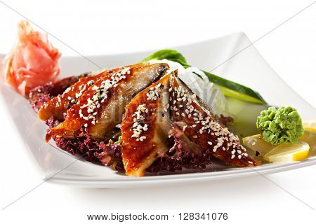 Unagi Sashimi - Smoked Eel on Daikon with Eel Sauce and Sesame. Served with Seaweed, Cucumber and Lemon