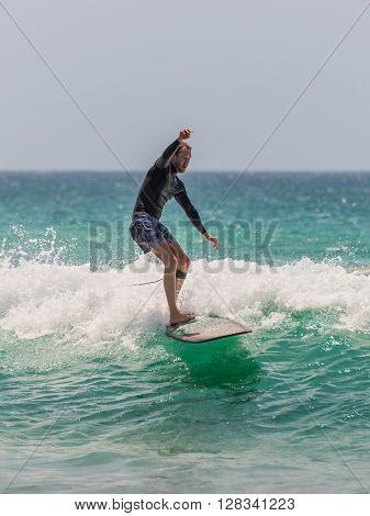 Manly Australia - November 9 2014: Man rides his surfboard towards the shore. Seven miles from the heart of Sydney famous Manly beach offers a wide range of sports and recreational activities.