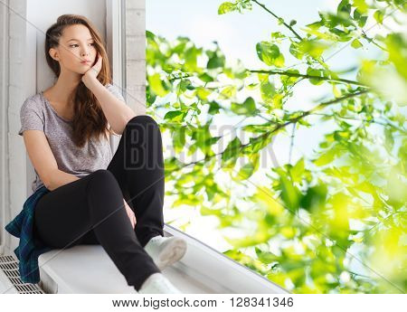 people, emotion and teens concept - sad unhappy pretty teenage girl sitting on windowsill looking trough window over green natural background