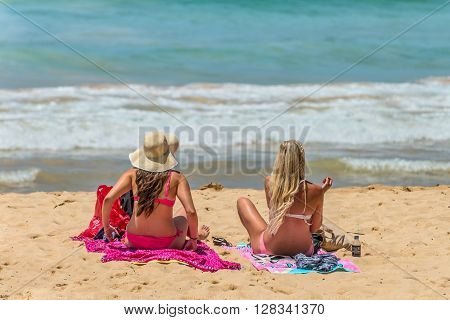 Manly Australia - November 9 2014: Ladies by the shore in Manly Beach in Manly Australia. Seven miles from the heart of Sydney famous Manly beach offers a wide range of sports and recreational activities.