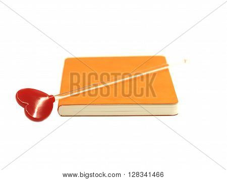 Red heart on the  orange book isolated on white background, select focus.