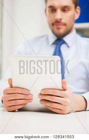 business, education, people and technology concept - close up of businessman with tablet pc in office