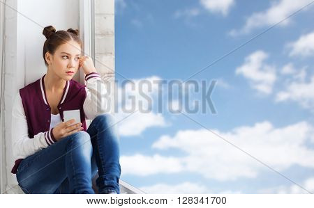 people, emotion, technology and teens concept - sad unhappy pretty teenage girl sitting on windowsill with smartphone and looking through window over blue sky and clouds background