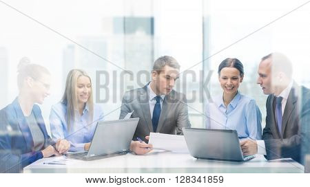 business, technology and office concept - smiling business team with laptop computers and documents having discussion in office