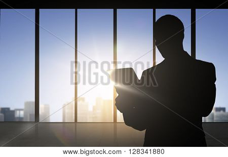 business and people concept - silhouette of business man with tablet pc over office window background