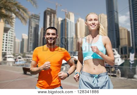 fitness, sport, exercising and healthy lifestyle concept - smiling couple running or jogging over dubai city street background